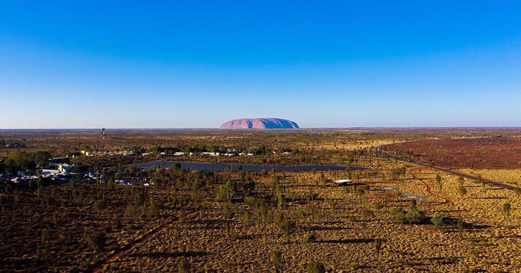 Aerial view of Uluru-Kata Tjuta National Park with Uluru rock formation in the background.